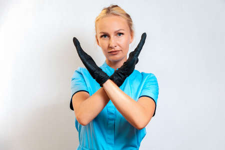 Prohibition. Portrait of cosmetologist woman in a uniform and balck latex gloves with crossed hands. White background. Concept of health and beauty industry.