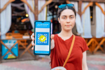 Vaccination. A young woman shows a smartphone with app of digital health passport. Covid-19 status. Outdoor. Concept of new normal.