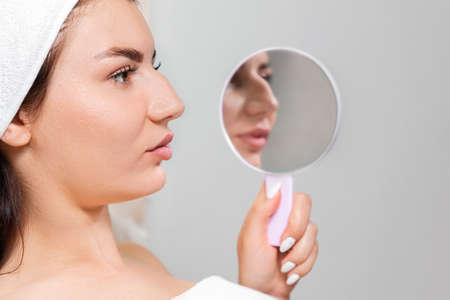 Comparison results before and after plastic surgery. A young woman holds a mirror with reflection of a humpback nose. Concept of rhinoplasty.