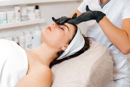 Professional beautician gives a facial massage to the client in salon. Close up. Concept of rejuvenation and beauty procedures. Stockfoto