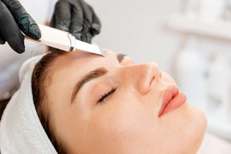 Procedure at the beauty salon. Cosmetologist cleans the client's forehead using a ultrasonic device. Close up. Concept of professional cosmetology.