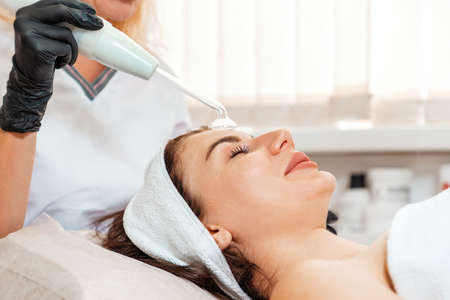 Darsonval cosmetology apparatus. Beautician cleans the client's forehead using a electric device. Concept of professional procedure in salon.