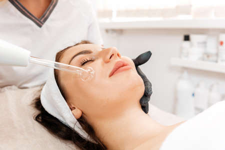 Darsonval cosmetology apparatus. Professional skin care in the salon. Woman on the darsonval therapy in beauty salon. Close up.