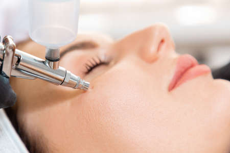 Face Beauty Treatment. Close up of client's face getting gas-liquid oxygen water epidermal peeling using hardware apparatus. Concept of cosmetology.