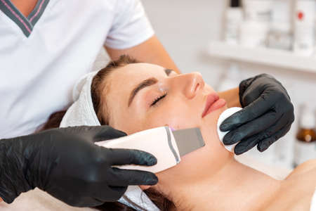 Beautician in rubber gloves cleans the client's cheak using a ultrasound device. Close up of face. Concept of beauty procedures and professional cosmetology.