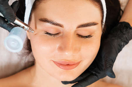 Face Beauty Treatment. Cosmetologist does a client's face gas-liquid oxygen water epidermal peeling using hardware apparatus. Top view and close up. Concept of salon cosmetology.