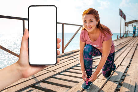 An adult smiling woman sitting down tying her shoelaces. In the background, the pier with the ship. Hand holding a smartphone with mock up. The concept of sport and a healthy lifestyle. Stockfoto