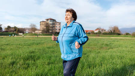 Running and sports activity. Portrait of mature smiling grandmother in sports clothes runs through a green field. The concept of the International Day of Older Persons.