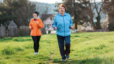 Happy caucasian grandmother and granddaughter running together. Old and young women in sports clothes, jogging in the park. International Day of Older Persons. The concept of a healthy lifestyle and sports. Stockfoto