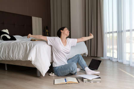 A young woman sits on the floor of a room and stretches after a long training session. The books are on the bed and on the floor. The concept of online education.