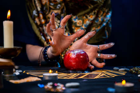A fortune teller conjures a red apple lying on the Tarot cards. On the table is a lighted candle and amulets. Close up. The concept of divination, astrology and esotericism. Stockfoto