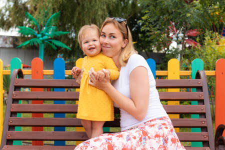 Funny portraits of a young mother with a happy little daughter. In the background, a colorful fence and amusement park. Happy children's Day concept.