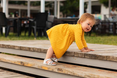 Cute smiling baby girl in yellow dress playing on the steps. Outdoors. The concept of a happy childhood and childhood autism. Stockfoto