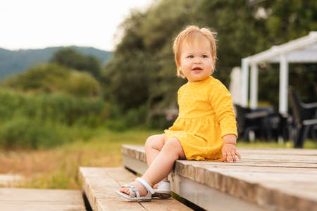 Summertime. Pretty smiling little girl in yellow dress sitting on the steps. Outdoors. The concept of a childhood autism.