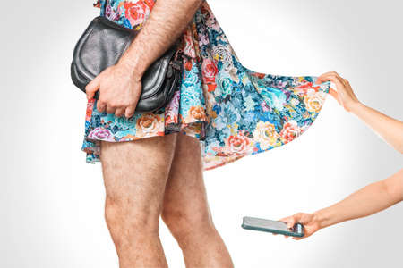 Sexual perverting and LGBT. A woman secretly take shot of the buttocks and underwear under the upped skirt of a transgender man. Side view, close-up. The concept of voyeurism.