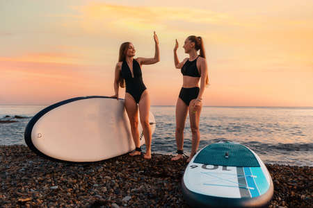 Two happy women stands on the beach with sup boards and high five with hands. In the background, the ocean and the sunset. Summer extreme recreation and surfing. Stockfoto
