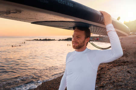 Portrait of caucasian man holding a sup board at his head and walking on the beach. In the background, the ocean and the sunset. Summer extreme recreation and surfing.