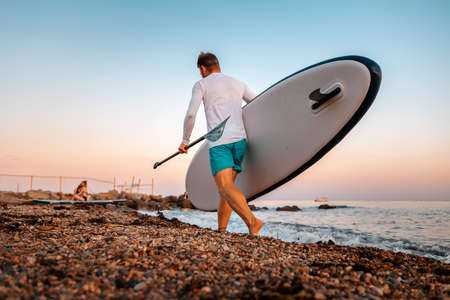 Fit man holding a sup board and paddle and walking on the beach. In the background, the ocean and the sunset. Back view. Summer surfing. Stockfoto