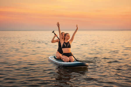 Summer surfing. Two happy women swimming on a sup board. In the background, the ocean and the sunset. Summer extreme recreation.