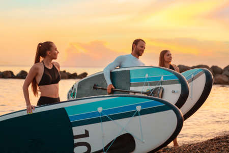 Summertime. Group of people walking on the beach with sup boards. In the background, the ocean and sunset. Copy space. Surfing.