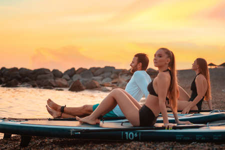 Summertime. Group of young people sitting on sup boards at the beach. In the background, the ocean and sunset. Copy space. Surfing and recreation.