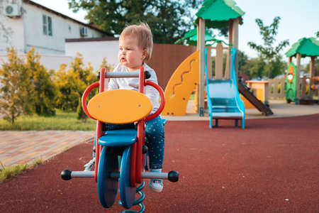Adorable baby playing on the playground, sitting on a wooden bike. Outdoors. Concept of autism and childhood.