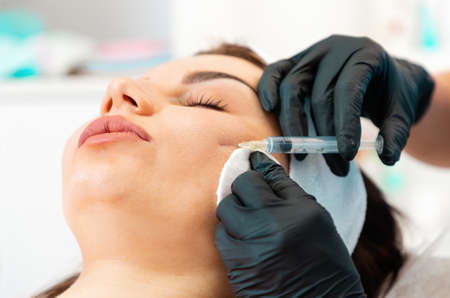 Close-up of woman's face getting injection in the cosmetology salon. Doctor in medical gloves with syringe injects cheek a hyaluronic acid. Concept of plastic surgery and face lifting.