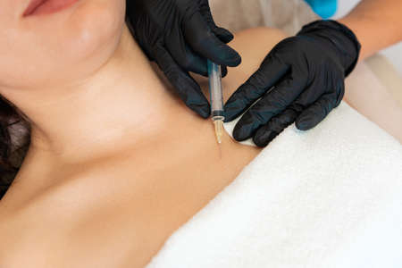 Professional cosmetologist makes an injection of hialuronic acid at breast of client's. Close up. Concept of plastic surgery and lifting.
