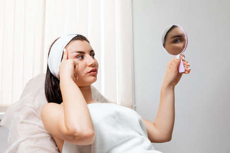 Caucasian beautiful woman looks in the mirror during a procedure in a cosmetology salon. The concept of plastic surgery and rejuvenation.