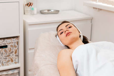 Aesthetic medicine. A young woman is lie on a couch during procedure in a cosmetology clinic.