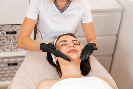 Professional cosmetologist gives a facial massage to the client in salon. Close up. Top view. Concept of Spa and beauty procedures.