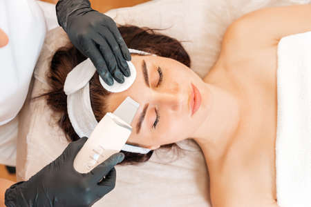 Cleaning procedure at the beauty salon. Cosmetologist cleans the client's forehead using a ultrasonic device. Close up. Top view. Concept of cosmetology and beauty.