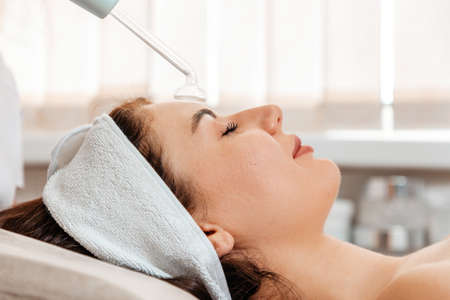 Darsonval cosmetology apparatus. Beautician cleans the client's forehead using a electric device. Close up. Professional rejuvenation procedure in salon.
