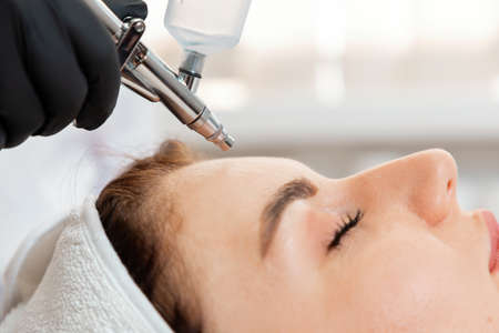 Beauty procedure of a gas-liquid oxygen water epidermal peeling using hardware apparatus to the client's face. Close up. Concept of cosmetology.