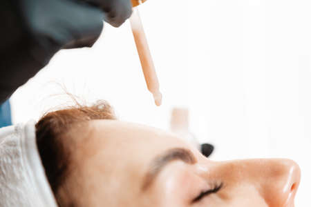 Cosmetology. Beautician drips a cosmetic serum on a female's forehead during the beauty procedure. Close-up. Professional skin care in salon. 版權商用圖片