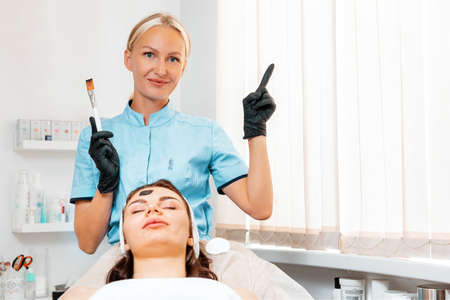 Professional salon cosmetology. Cosmetolog in latex gloves holding a mask brush and show with index finger at right side. Client lie on the procedure. Copy space.