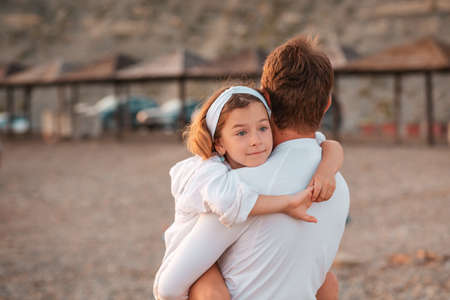 Father's Day. Father embracing his daughter in arms. Back view. Outdoor. Concept of happy fatherhood, parenting and adoption of children.