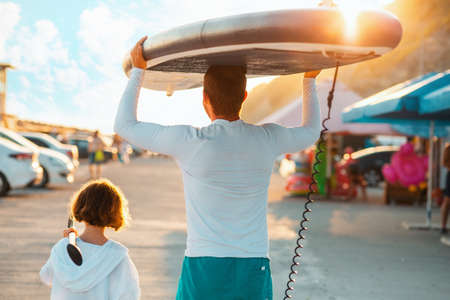 Summer family vacation. Father and daughter are walking along the beach. Man holding a sup board and girl holds a paddle. Back view. Sunset light.