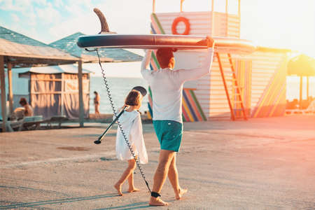 Father and daughter are walking along the beach. Man holding a sup board. Back view. Sunset light. Summer family vacation.