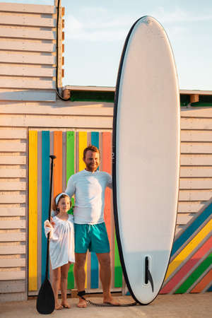 Summer holidays. Father and daughter posing with sup board. Man holding a sup board, and girl holds a paddle. Vertical. Sunset light.