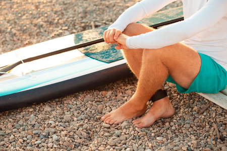 A man sitting at the pebble beach with a sup board. Feet and surfboard close up. Summer recreation and activity.