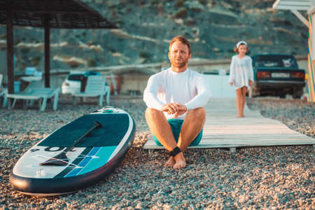 Summertime. Father sitting and relax at beach. Sup board lie near man. On the defocused background walking preschool girl. Family vacation at the sea.