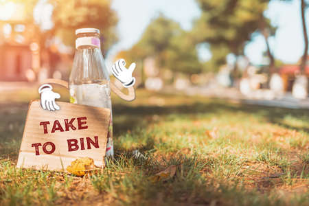 The concept of environmental pollution and waste sorting. A glass bottle with cartoon hands holds a cardboard abeled TAKE to BIN. In the background, grass and sunlight. Copy space.