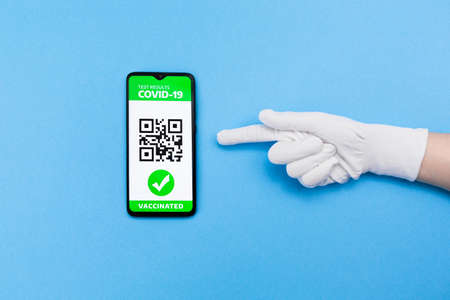 Hand in glove point on cellphone screen with electronic Immunity passport with a COVID-19 vaccination. Blue background. Flat lay. Concept of vaccination and digital passport.