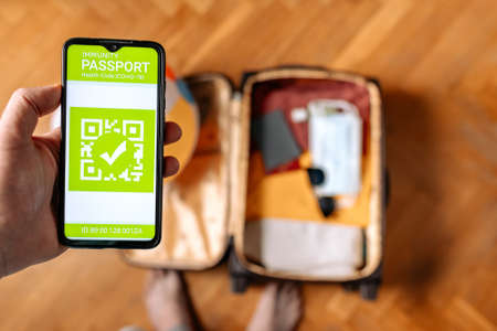 The concept of new normal. Top view of a male hand holds a smartphone with an immune digital health passport. A suitcase with clothes and protective masks on the blurred background.