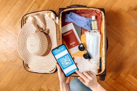 New normal concept. A woman hold a smartphone with an immune digital health passport at her hand. In the background, a suitcase with clothes and protective masks and straw hat in a blur. Flat lay.