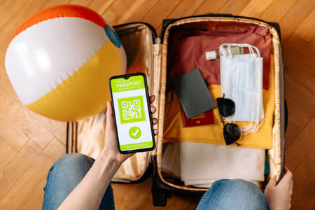 A woman holds a smartphone with an immune digital health passport in her hand. A negative test for the virus is covid-19. Flat lay. Close-up of a hand and a suitcase with clothes and virus protection equipment.