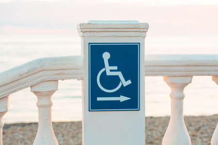 International Disability Day. A blue sign with a handicapped person on the public beach. Concept of care of disabled people.