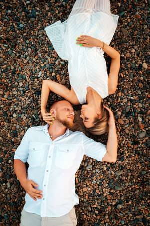 Valentines day. Beautiful couple of young caucasians man and woman lie on a pebbles beach, at romantic date. Vertical. Top view.