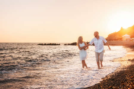 Just married. A happy young man and woman are having fun walking along the seashore. In the background, the sunset and the sky. Copy space. Concept of honeymoon.